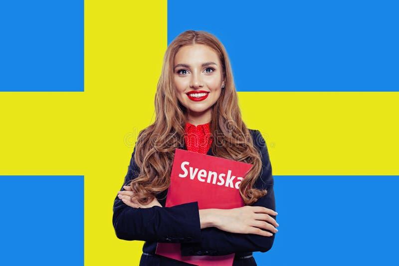Ευτυχής σπουδαστής γυναικών με την κενή κάλυψη βιβλίων στο υπόβαθρο σημαιών της Σουηδίας Χαμόγελο κοριτσιών στοκ φωτογραφία με δικαίωμα ελεύθερης χρήσης
