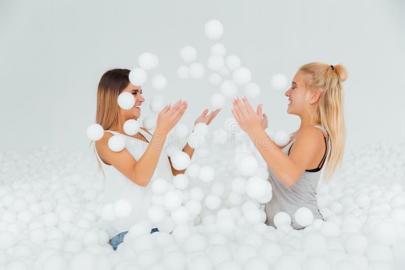 Ευτυχής στάση φίλων πορτρέτου που περιβάλλεται από τις άσπρες πλαστικές σφαίρες στην ξηρά λίμνη στοκ φωτογραφία