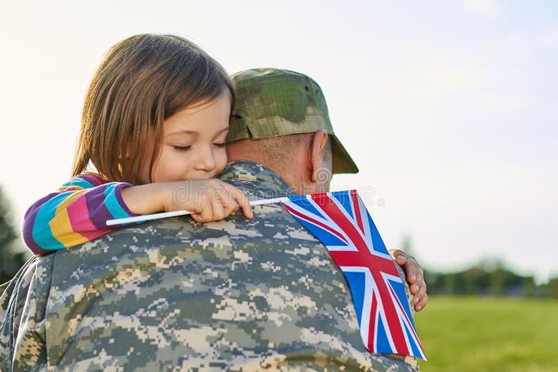 Ευτυχής συγκέντρωση του βρετανικού στρατιώτη και της μικρής κόρης του στοκ φωτογραφίες