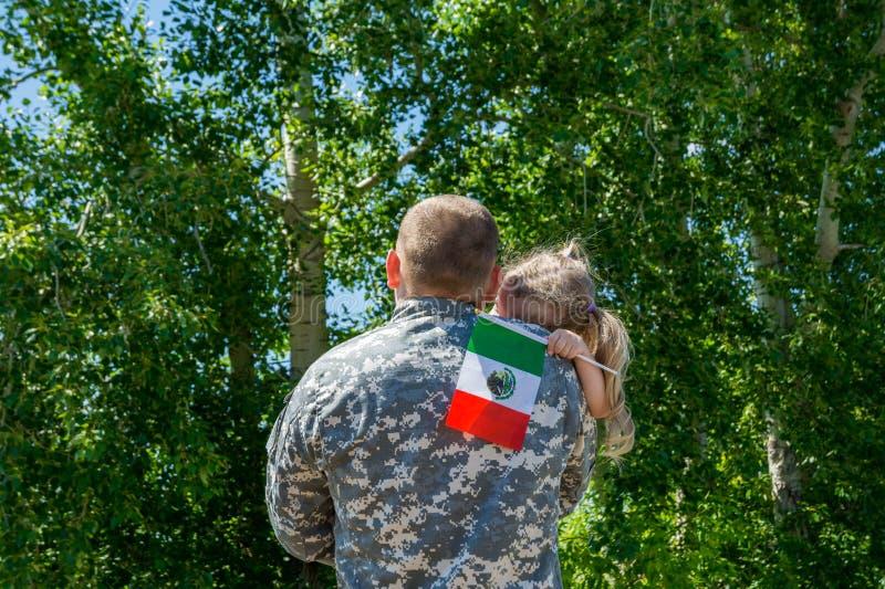 Ευτυχής συγκέντρωση του στρατιώτη από το Μεξικό με την οικογένεια, πατέρας αγκαλιάσματος κορών στοκ φωτογραφία με δικαίωμα ελεύθερης χρήσης