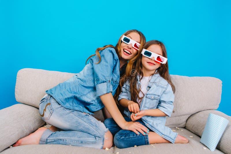 Ευτυχής συγκινημένη μητέρα με τη χαριτωμένη όμορφη κόρη στον καναπέ στο μπλε υπόβαθρο Τρισδιάστατος κινηματογράφος προσοχής στα γ στοκ εικόνα με δικαίωμα ελεύθερης χρήσης