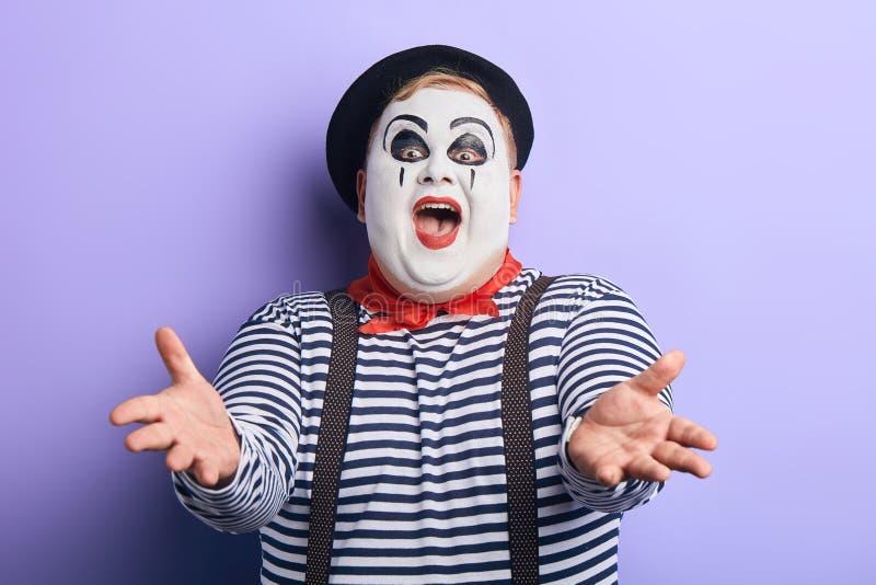 Ευτυχής συγκινημένος αρσενικός καλλιτέχνης mime που τεντώνει τα όπλα του στοκ εικόνες με δικαίωμα ελεύθερης χρήσης