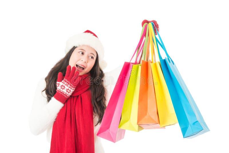 Ευτυχής συγκινημένος θηλυκός αγοραστής που παρουσιάζει αγορές με το καπέλο santa στοκ φωτογραφία