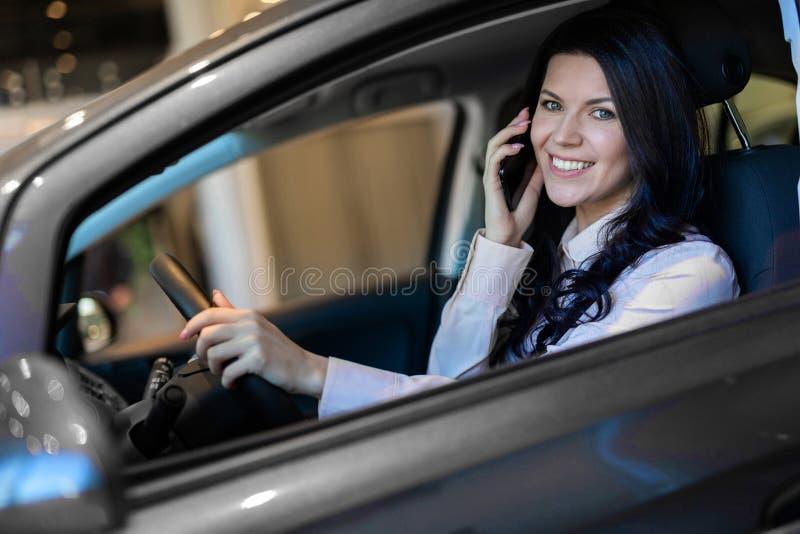 Ευτυχής συνεδρίαση αγοραστών γυναικών στο νέο όχημά της στη εμπορία αυτοκινήτων στοκ εικόνες με δικαίωμα ελεύθερης χρήσης