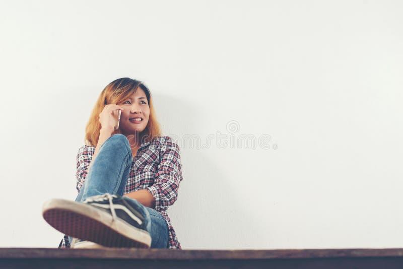 Ευτυχής συνεδρίαση γυναικών hipster στο ξύλινο πάτωμα που μιλά με το τηλέφωνο α στοκ φωτογραφία με δικαίωμα ελεύθερης χρήσης