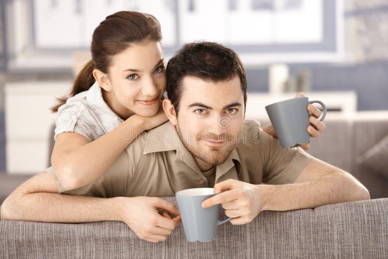 Ευτυχής συνεδρίαση ζευγών στον καναπέ στην αρμονία στοκ φωτογραφία με δικαίωμα ελεύθερης χρήσης