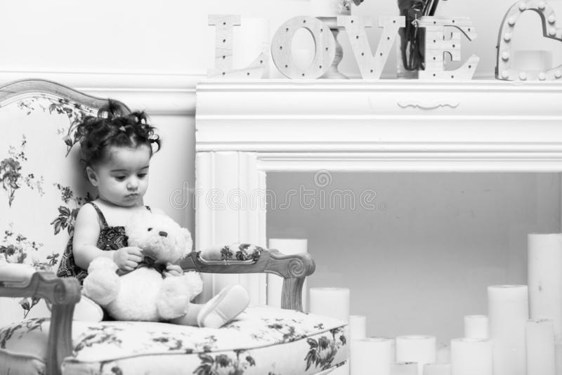 Ευτυχής συνεδρίαση κοριτσάκι χαμόγελου γλυκιά στην πολυθρόνα, πορτρέτο κοριτσιών στοκ εικόνες