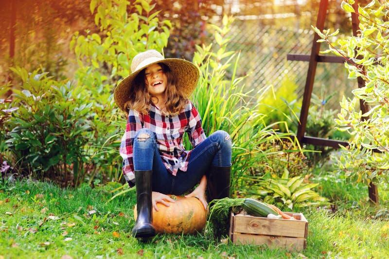 Ευτυχής συνεδρίαση κοριτσιών παιδιών αγροτών με τη συγκομιδή φθινοπώρου στον κήπο στοκ εικόνες με δικαίωμα ελεύθερης χρήσης