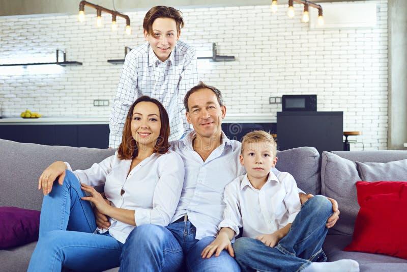 Ευτυχής συνεδρίαση οικογενειακού χαμόγελου στον καναπέ στο δωμάτιο στοκ φωτογραφία