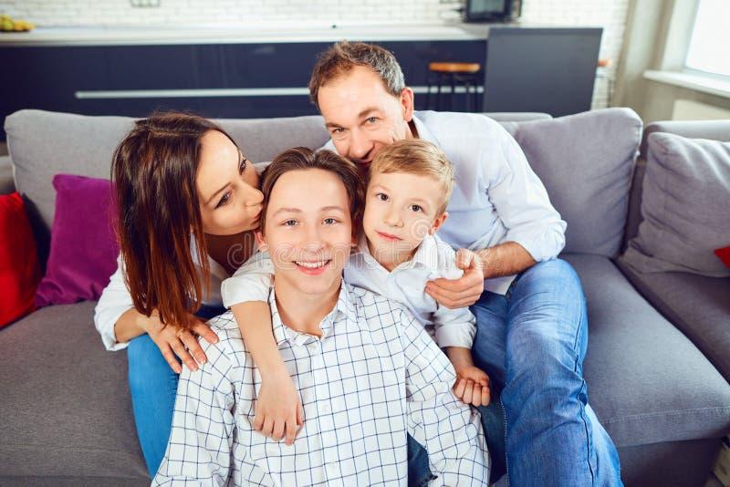 Ευτυχής συνεδρίαση οικογενειακού χαμόγελου στον καναπέ στο δωμάτιο στοκ εικόνα με δικαίωμα ελεύθερης χρήσης
