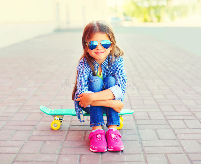 Ευτυχής συνεδρίαση παιδιών μικρών κοριτσιών χαμόγελου μόδας skateboard στοκ εικόνα με δικαίωμα ελεύθερης χρήσης