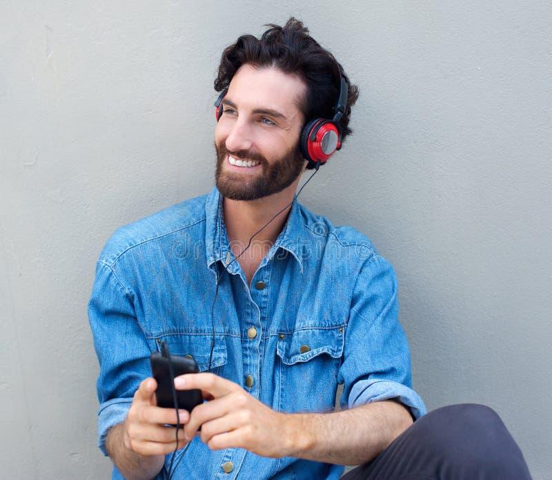 Ευτυχής συνεδρίαση ατόμων με τα ακουστικά και το κινητό τηλέφωνο στοκ εικόνες με δικαίωμα ελεύθερης χρήσης