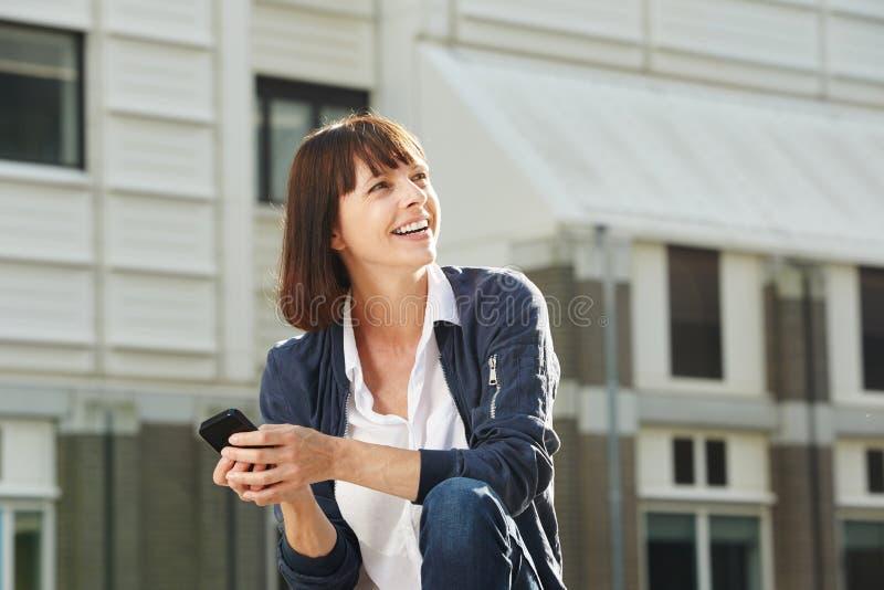 Ευτυχής συνεδρίαση γυναικών έξω στην πόλη με το έξυπνο τηλέφωνο στοκ εικόνα με δικαίωμα ελεύθερης χρήσης