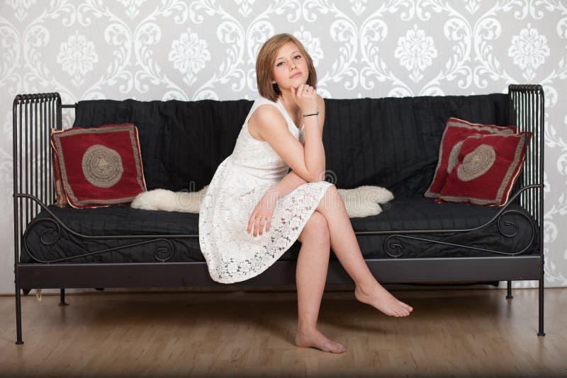 Ευτυχής συνεδρίαση γυναικών σε έναν καναπέ στοκ εικόνες