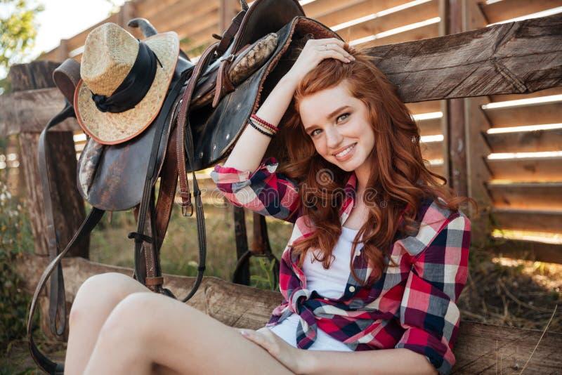 Ευτυχής συνεδρίαση γυναικών cowgirl στο αγρόκτημα στοκ φωτογραφίες με δικαίωμα ελεύθερης χρήσης