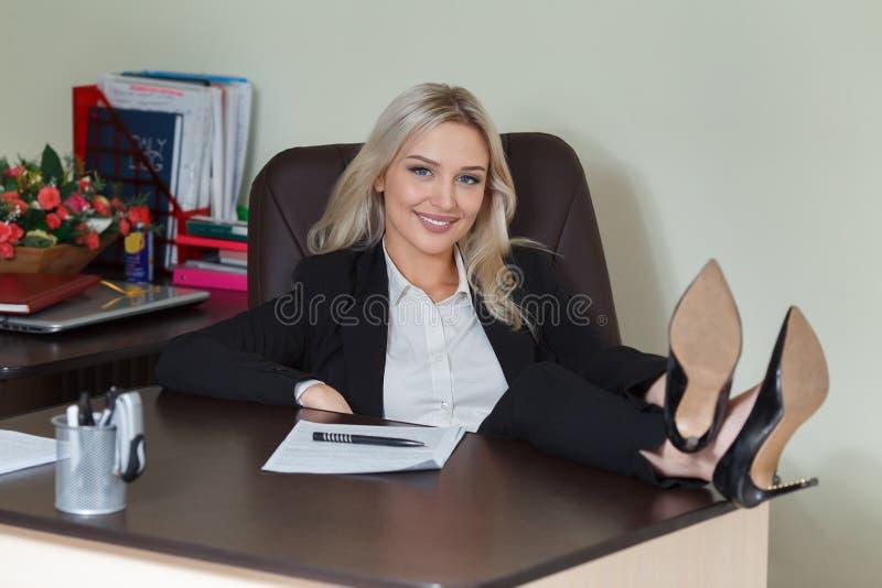 Ευτυχής συνεδρίαση επιχειρηματιών με τα πόδια της επάνω στο γραφείο της στοκ φωτογραφία