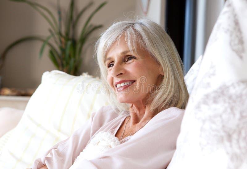 Ευτυχής συνεδρίαση ηλικιωμένων γυναικών στον καναπέ που χαλαρώνουν και που χαμογελά στοκ εικόνες με δικαίωμα ελεύθερης χρήσης