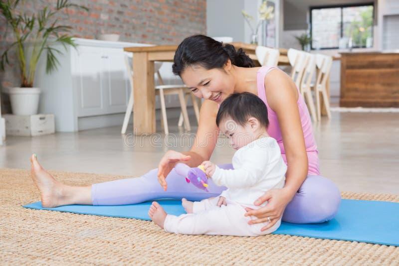 Ευτυχής συνεδρίαση κορών μητέρων και μωρών στην άσκηση του χαλιού στοκ φωτογραφία με δικαίωμα ελεύθερης χρήσης