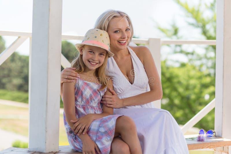 Ευτυχής συνεδρίαση μητέρων και κορών στον πάγκο στο θερινό σπίτι στοκ εικόνα