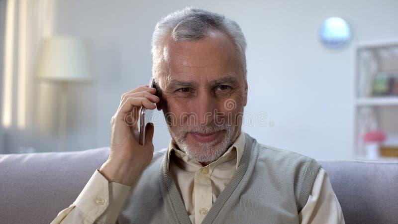 Ευτυχής συνταξιούχος που μιλά στο τηλέφωνο με τους στενούς συγγενείς, φτηνός κινητός προμηθευτής στοκ φωτογραφίες