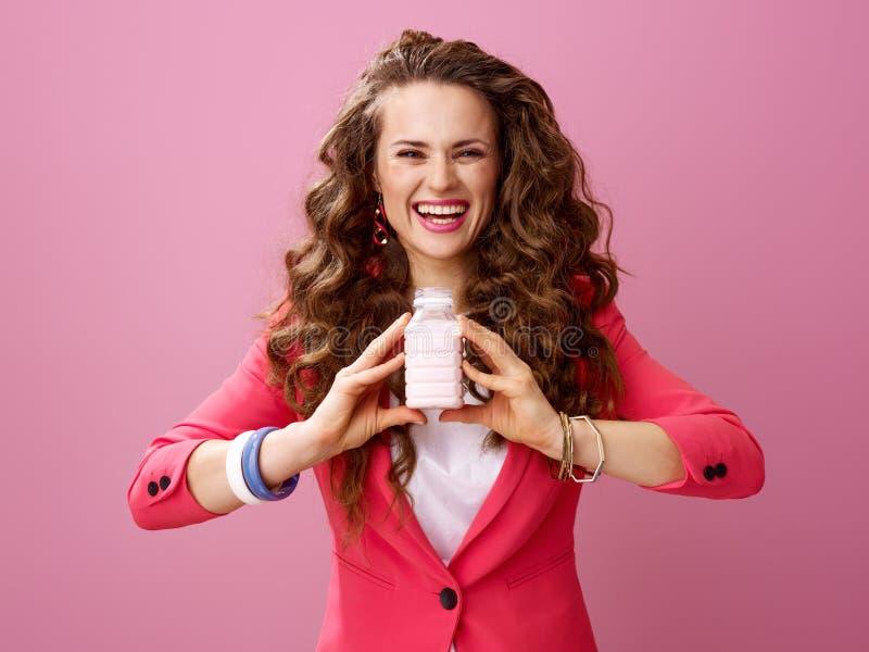 Ευτυχής σύγχρονη γυναίκα στο ροζ που παρουσιάζει στο αγρόκτημα οργανικό γιαούρτι στοκ φωτογραφίες