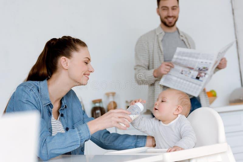 ευτυχής ταΐζοντας γιος μητέρων με το γάλα στο μπουκάλι μωρών στον πατέρα κουζινών στοκ εικόνες με δικαίωμα ελεύθερης χρήσης