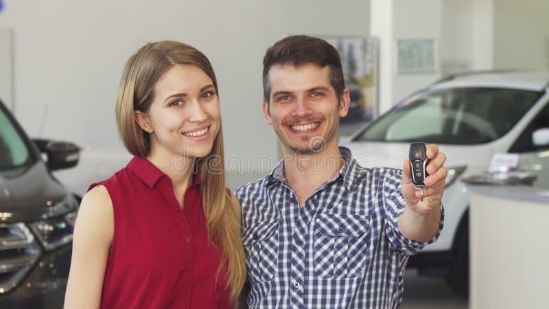 Ευτυχής τοποθέτηση ζευγών με τα κλειδιά αυτοκινήτων για το νέο αυτοκίνητό τους στοκ φωτογραφία