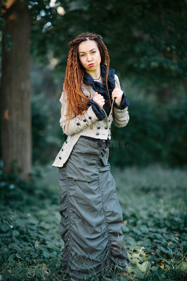 Ευτυχής τοποθέτηση κοριτσιών dreadlocks μοντέρνη στο δάσος στοκ εικόνες