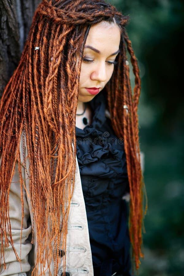 Ευτυχής τοποθέτηση κοριτσιών dreadlocks μοντέρνη στο δάσος στοκ φωτογραφία