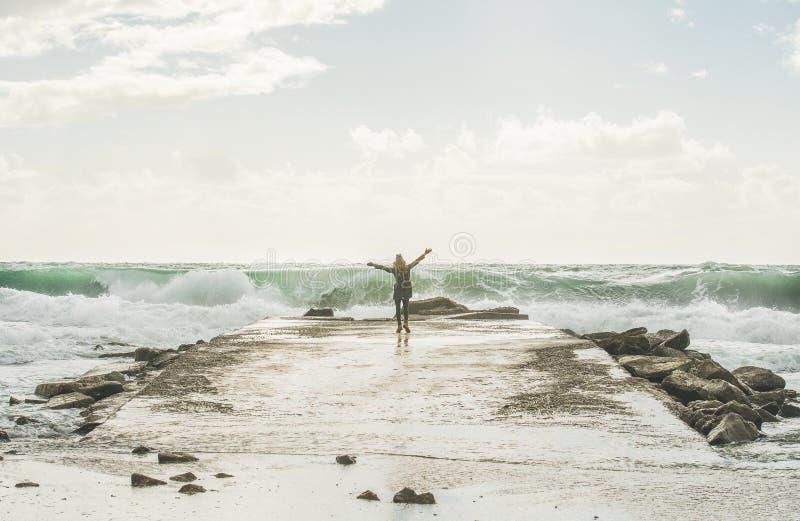 Ευτυχής τουρίστας γυναικών που απολαμβάνει τα κύματα της θυελλώδους Μεσογείου στοκ φωτογραφία