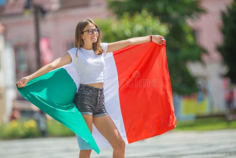 Ευτυχής τουρίστας κοριτσιών που περπατά στην οδό με την ιταλική σημαία στοκ εικόνες