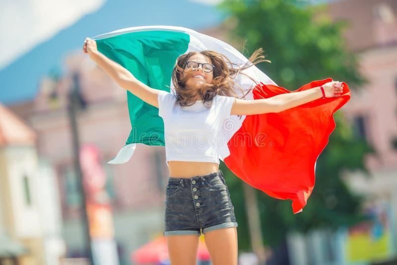 Ευτυχής τουρίστας κοριτσιών που περπατά στην οδό με την ιταλική σημαία στοκ φωτογραφίες