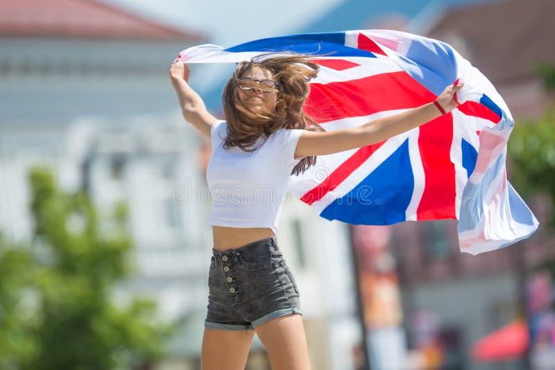 Ευτυχής τουρίστας κοριτσιών που περπατά στην οδό με τη σημαία της Μεγάλης Βρετανίας στοκ εικόνα