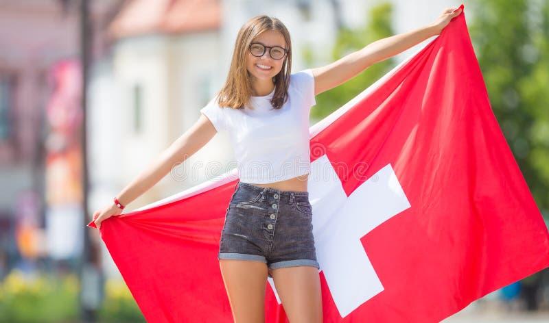 Ευτυχής τουρίστας κοριτσιών που περπατά στην οδό με τη σημαία της Ελβετίας στοκ φωτογραφίες με δικαίωμα ελεύθερης χρήσης