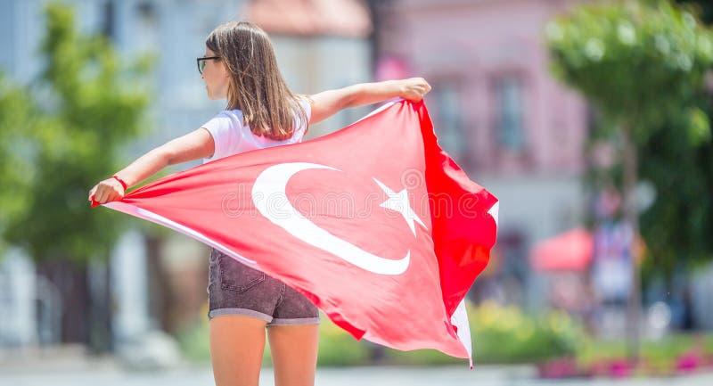 Ευτυχής τουρίστας κοριτσιών που περπατά στην οδό με τη σημαία της Τουρκίας στοκ φωτογραφία