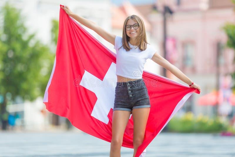 Ευτυχής τουρίστας κοριτσιών που περπατά στην οδό με τη σημαία της Ελβετίας στοκ φωτογραφία με δικαίωμα ελεύθερης χρήσης