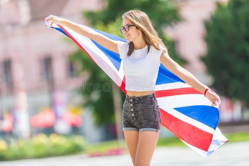 Ευτυχής τουρίστας κοριτσιών που περπατά στην οδό με τη σημαία της Μεγάλης Βρετανίας στοκ εικόνα με δικαίωμα ελεύθερης χρήσης