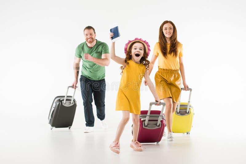 Ευτυχής τρέχοντας οικογένεια με τις βαλίτσες στοκ εικόνες