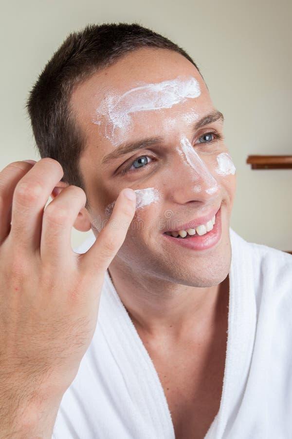 Ευτυχής τύπος που βάζει την κρέμα προσώπου με το δάχτυλό σας στοκ φωτογραφία με δικαίωμα ελεύθερης χρήσης