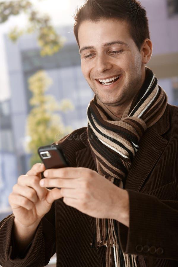 Ευτυχής τύπος που εξετάζει το κινητό τηλέφωνο στοκ εικόνες