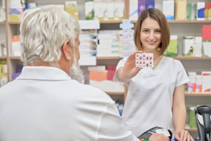 Ευτυχής φαρμακοποιός που παρουσιάζει πακέτο φουσκαλών των χαπιών στοκ φωτογραφία με δικαίωμα ελεύθερης χρήσης