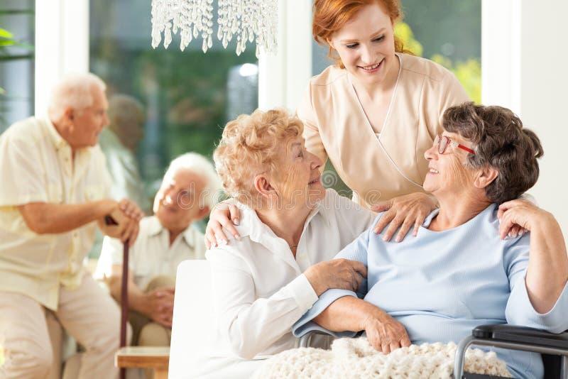 Ευτυχής φιλία στη μεγάλη ηλικία Προσφορά caregiver που στέκεται πίσω από το SE στοκ φωτογραφία