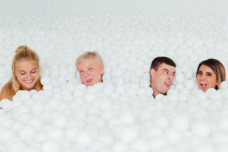 Ευτυχής φιλική οικογένεια που περιβάλλεται από τις άσπρες πλαστικές σφαίρες στην ξηρά λίμνη στοκ εικόνες