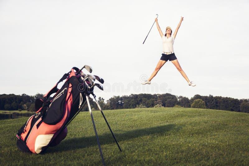 Ευτυχής φορέας γκολφ που πηδά στο γήπεδο του γκολφ. στοκ εικόνα