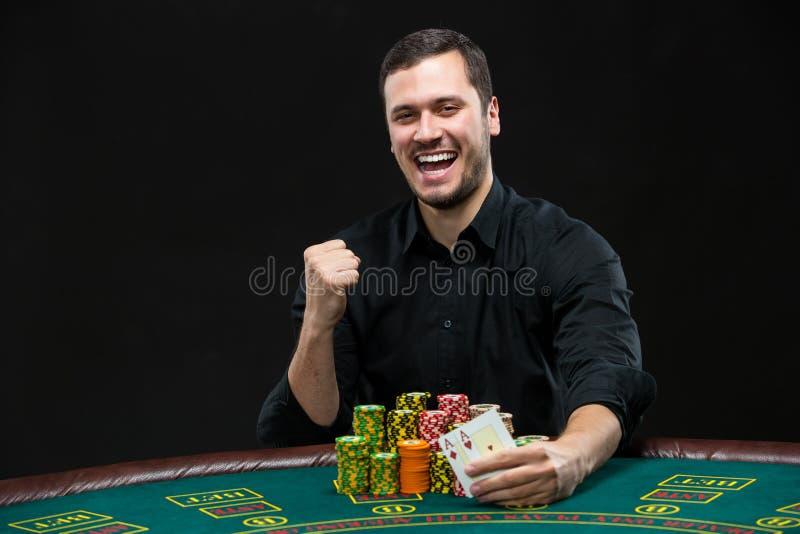 Ευτυχής φορέας πόκερ που κερδίζει και που κρατά ένα ζευγάρι των άσσων στοκ εικόνες