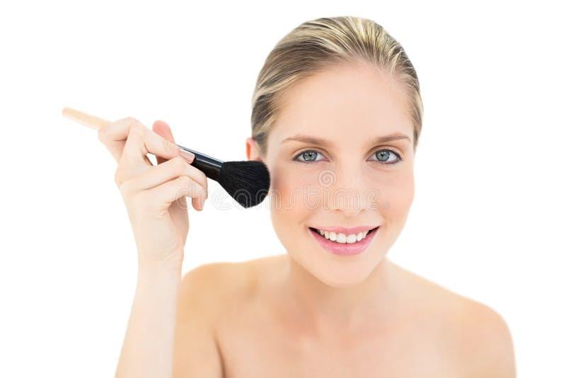 Ευτυχής φρέσκια ξανθή γυναίκα που εφαρμόζει τη σκόνη στα μάγουλά της στοκ φωτογραφίες