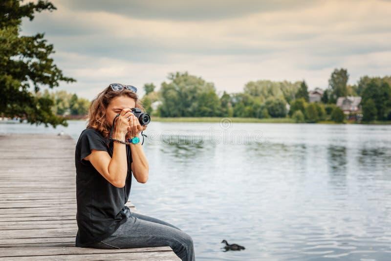 Ευτυχής φωτογράφος γυναικών που κρατά την επαγγελματική ψηφιακή κάμερα και στοκ φωτογραφίες