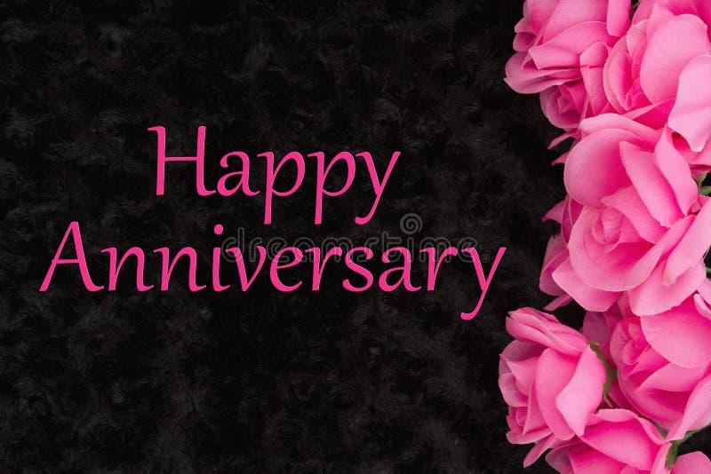 Ευτυχής χαιρετισμός επετείου με τα ρόδινα τριαντάφυλλα στο Μαύρο στοκ εικόνες