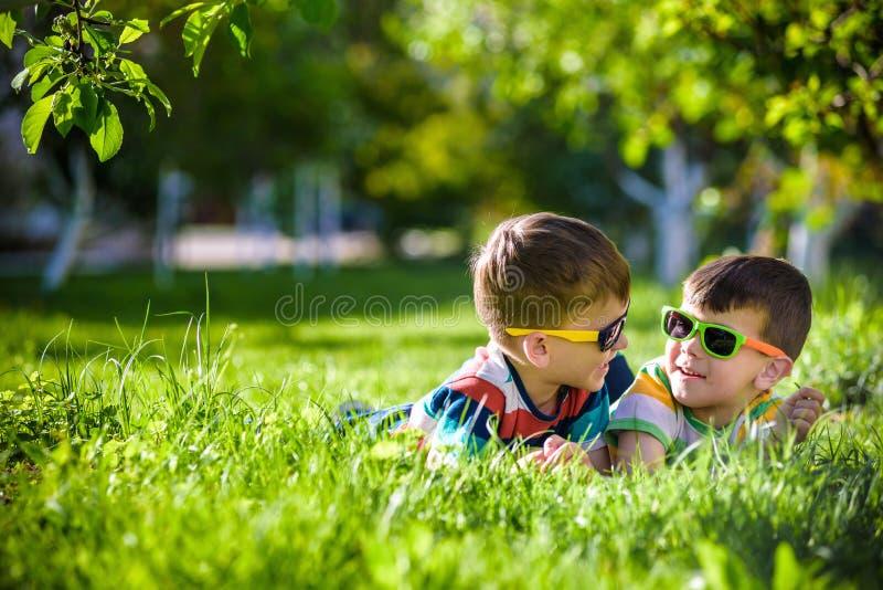 Ευτυχής χαλάρωση αδελφών αμφιθαλών αγοριών χαμόγελου στη χλόη Το στενό u στοκ φωτογραφία με δικαίωμα ελεύθερης χρήσης