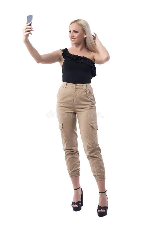 Ευτυχής χαλαρωμένη όμορφη ξανθή νέα τοποθέτηση τρίχας ρύθμισης γυναικών για το selfie στοκ φωτογραφία